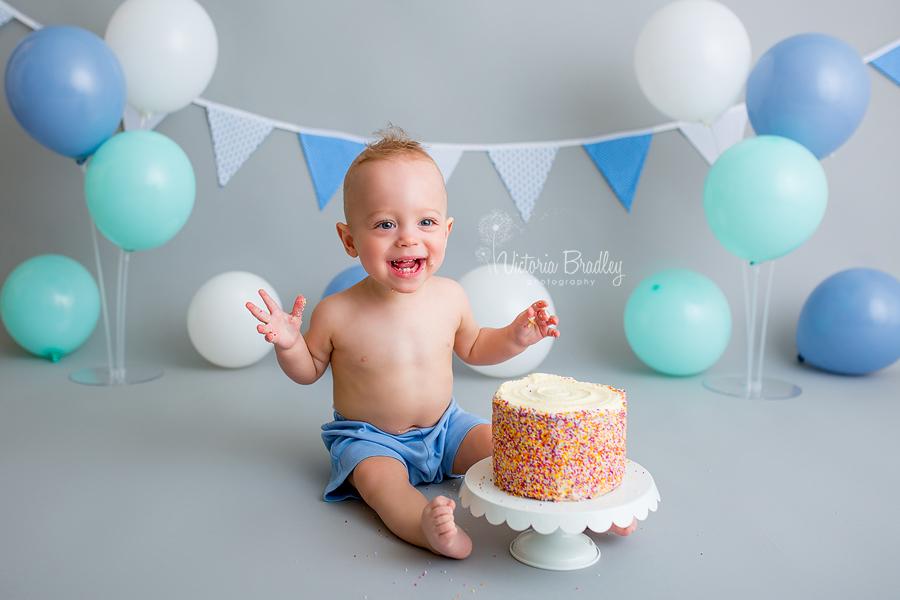 rainbow cake, cake smash, grey backdrop and blue and white balloons