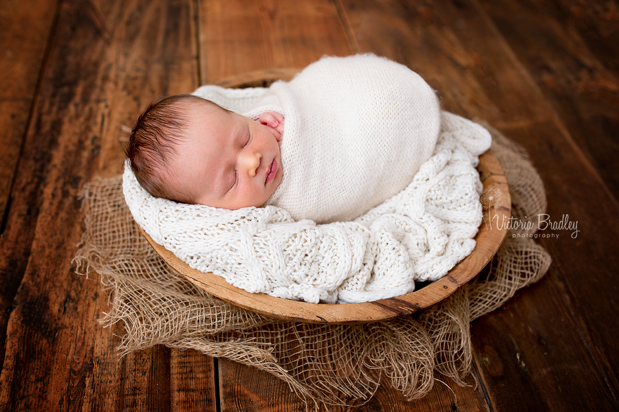 cream and dark wood with newborn with knitted cream wrap