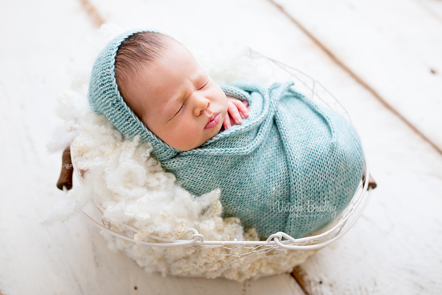 wrapped newborn with light jade knitted wrap