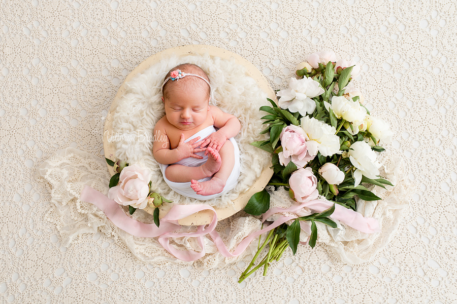 newborn baby in wooden bowl with flowers