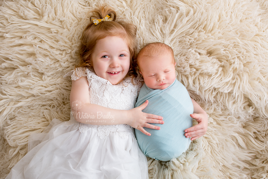 sibling and newborn shots on cram flokati