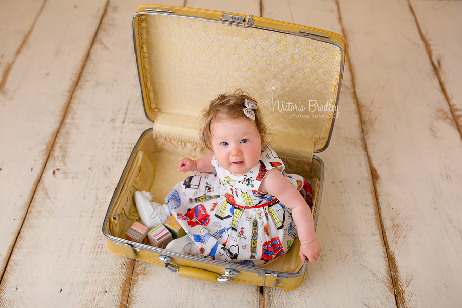 sitter baby girl in yellow suitcase with london print dress