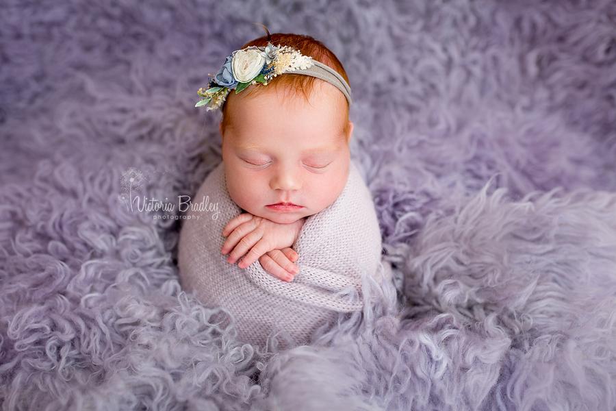 potato sack pose, newborn baby girl on lilac flokati