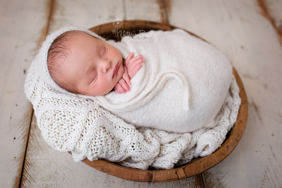 wrapped newborn boy in cream knitted wrap
