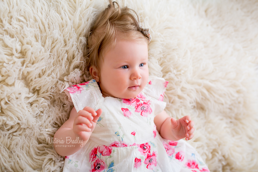 baby girl lay on cream flokati rug, sitter photographer