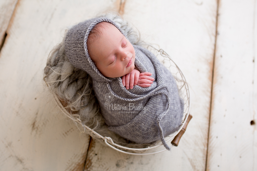 grey knitted wrap and bonnet on newborn baby boy