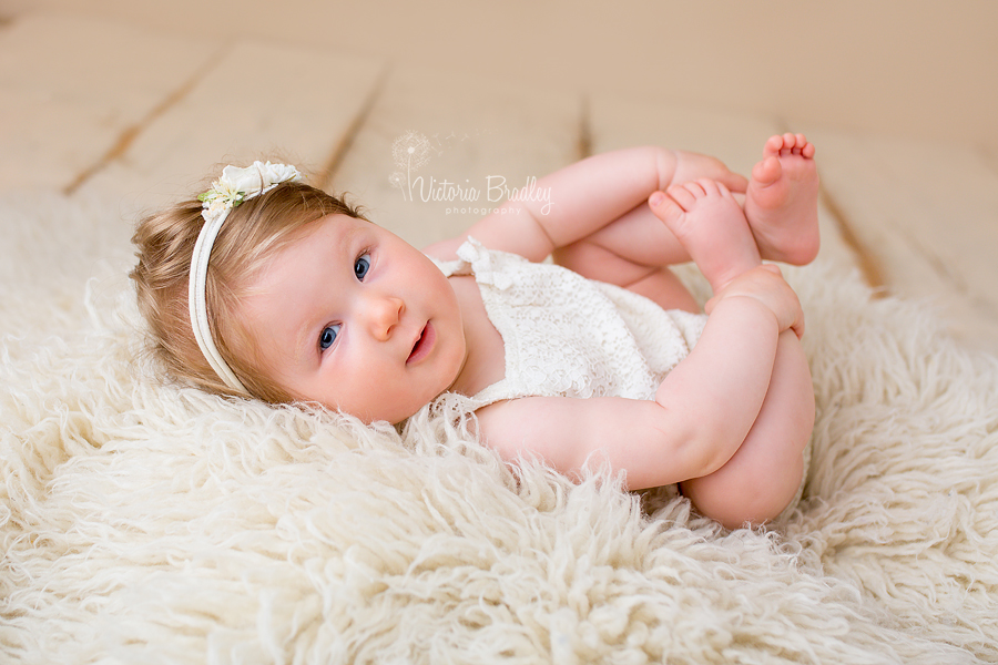 baby girl in cream romper during her nottinghamshire baby photography session
