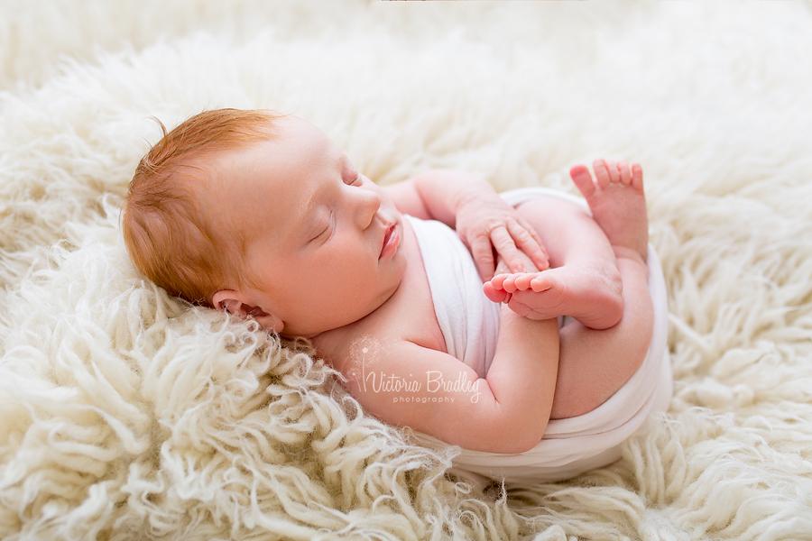 egg wrap newborn pose, on cream flokati with pale pink wrap