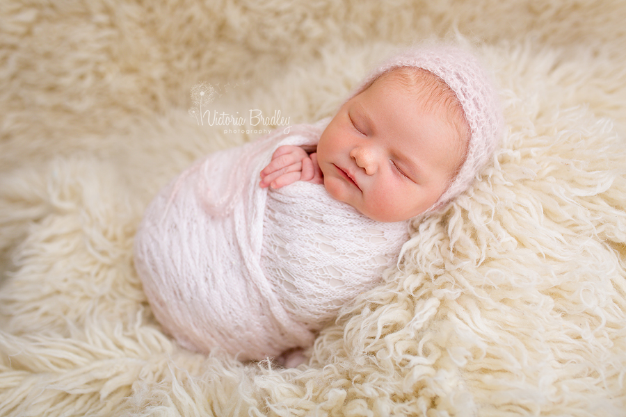 wrapped baby during a newborn photography session, in a pink knitted wrap with pink bonnet