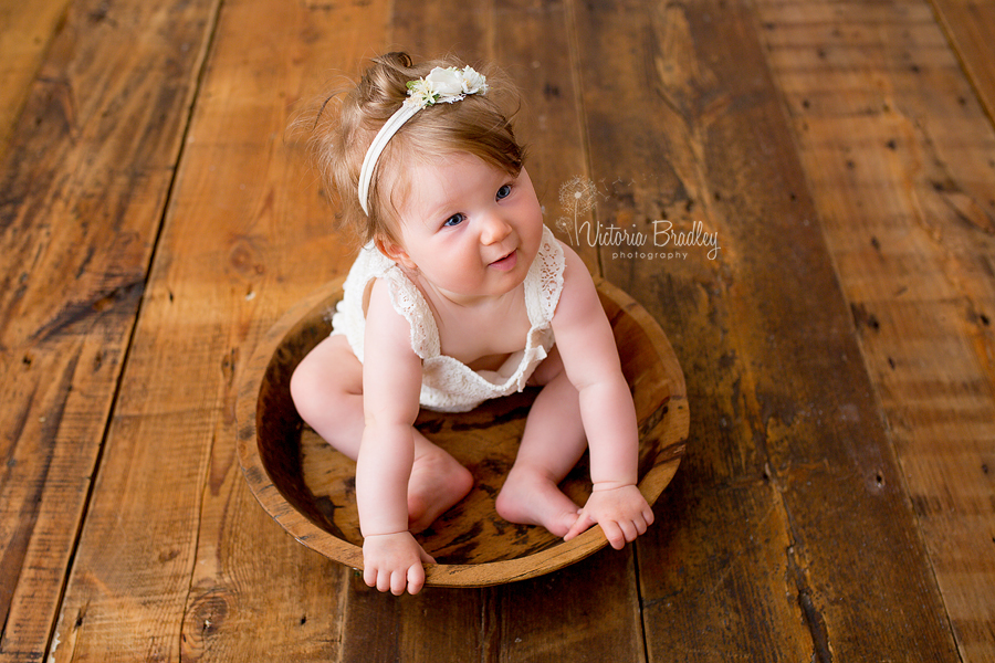 baby girl sat in wooden bowl during photography session