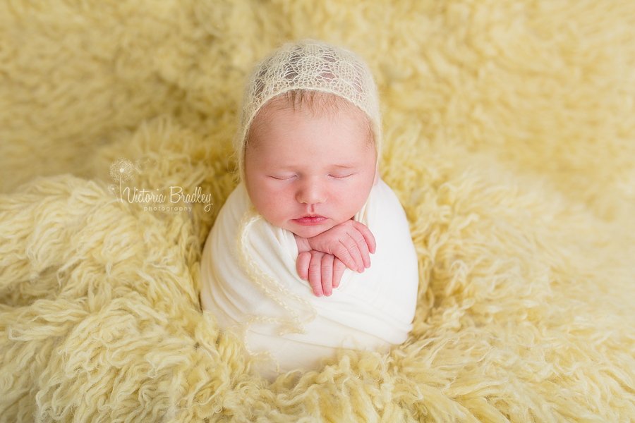 potato sack pose newborn baby girl on lemon flokati rug