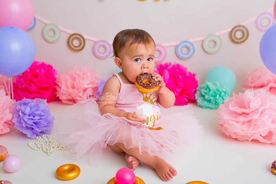 doughnut cake smash baby girl eating a chocolate doughnut