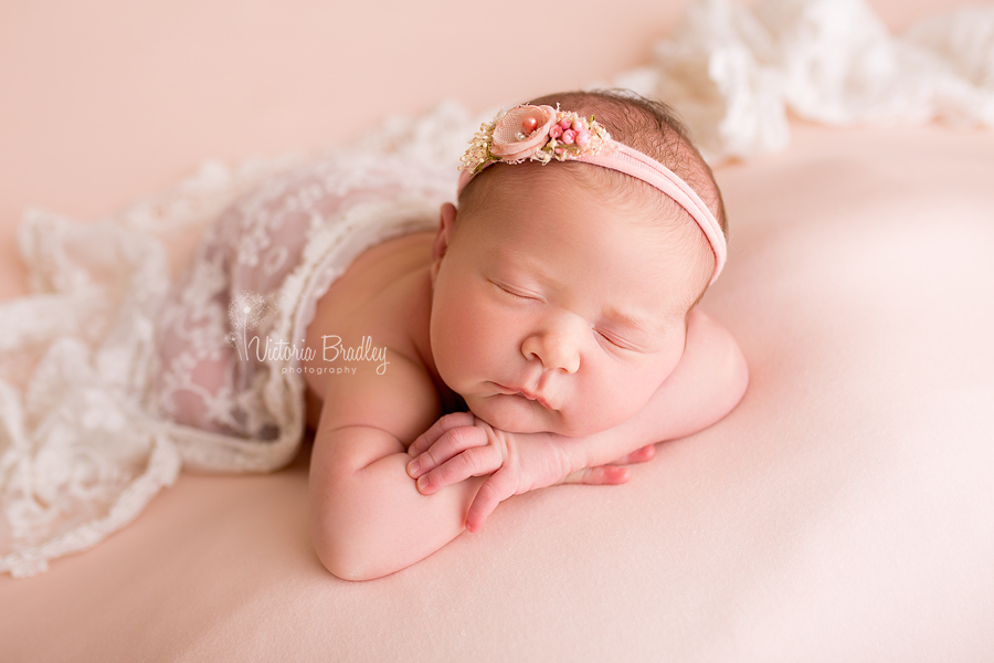 peach backdrop with newborn baby, with peach tie-back