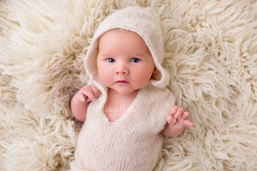 baby boy with cram knitted hoodie on cram flokati