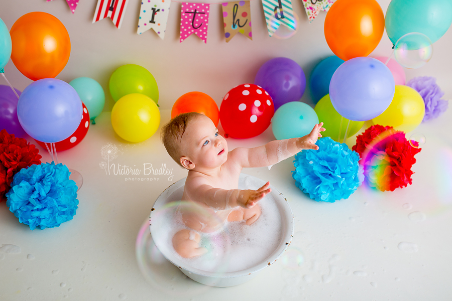 rainbow cake smash vintage white bath tub baby boy catching bubbles