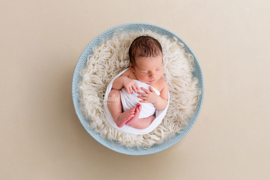 wrapped newborn boy in blue basket