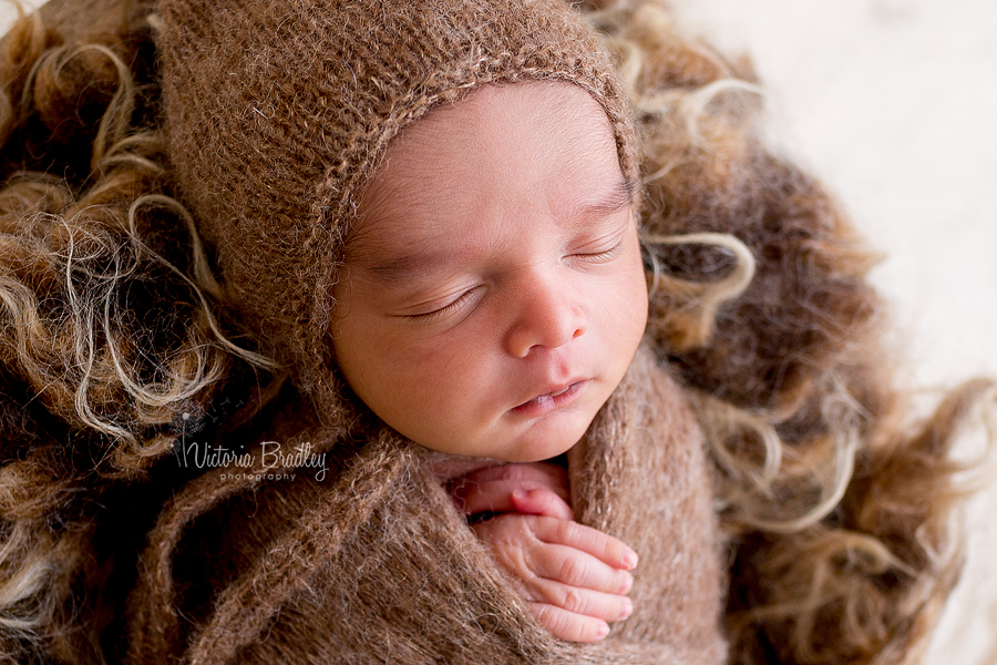 wrapped newborn in brown wrap and bonnet