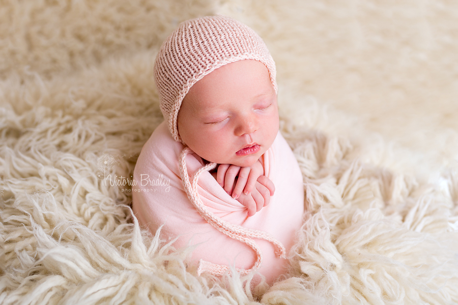 wrapped newborn baby girl in peach wrap on a cream flokati, potato sack pose newborn photography session