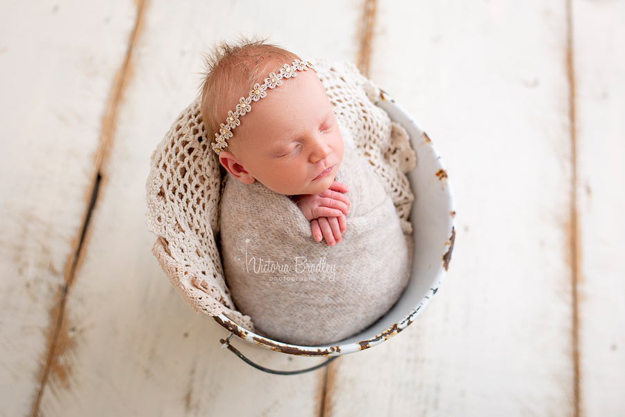 wrapped baby girl in white bucket