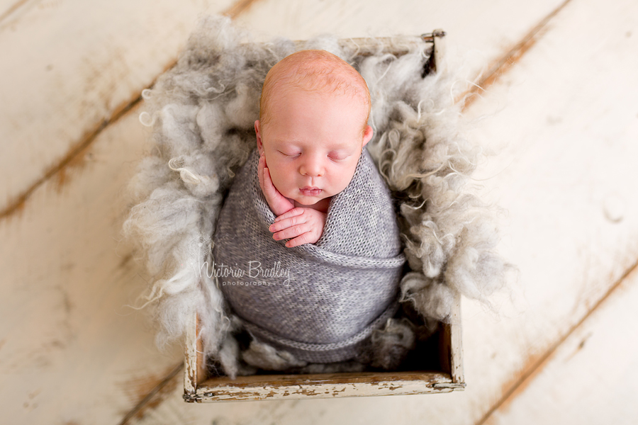newborn baby boy photography session wrapped baby in grey