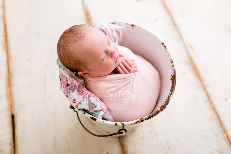wrapped newborn baby girl in peach wrap on a in a white bucket, newborn photography studio nottinghamshire