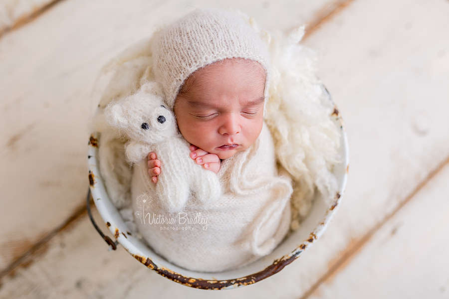 newborn holding tiny teddy in cream kitted wrap and bonnet