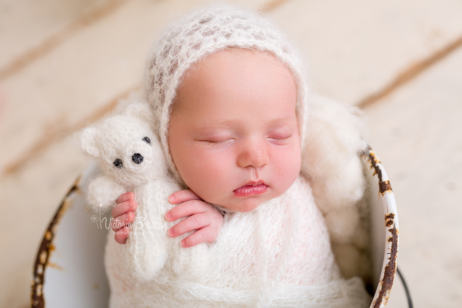 wrapped newborn baby girl in cream knitted wrap with cream bonnet and tidy teddy