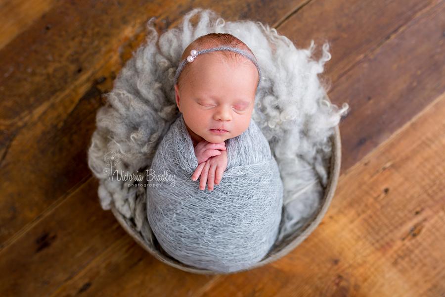 newborn baby in grey wrap