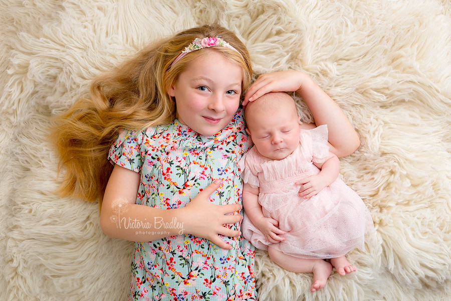 newborn baby girl photography with sibling on cream flokati in floral dress
