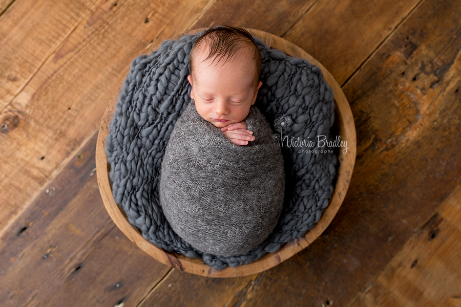 wrapped newborn baby boy photography session, grey wrap in a wooden bowl on wooden floor
