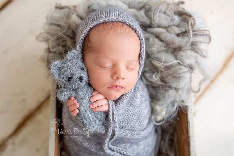 baby in white grey knitted wrap holding grey teddy