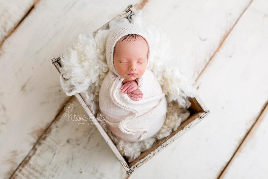 wrapped newborn baby boy photography sessions cream knitted wrap in a cream crate