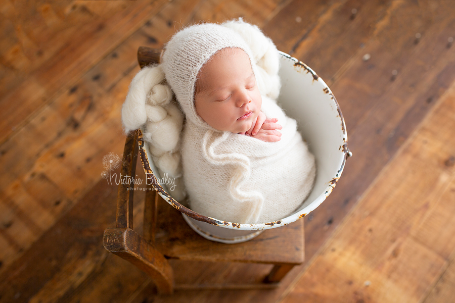 newborn photography session wrapped baby in bucket