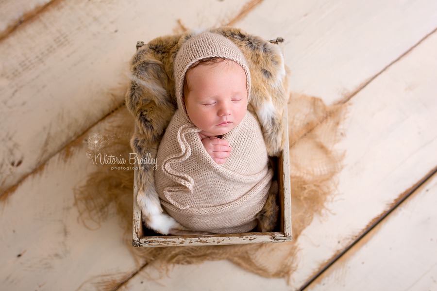 wrapped baby newborn in cream wrap with cream bonnet, in cream crate with fur, hessian and cream wooden painted floor