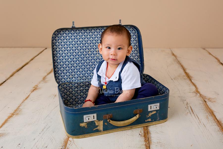 baby boy in blue suitcase