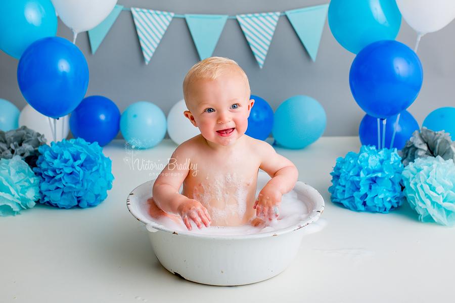 bath tub splash session, white tub on grey backdrop with blue ballons