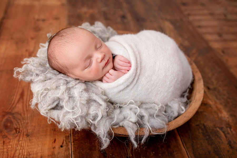 wrapped baby newborn on grey fur in wooden bowl