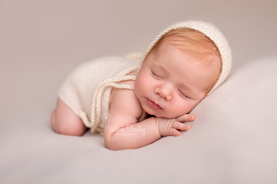 sleepy newborn boy on biscuit backdrop with cream knitted bonnet and wrap