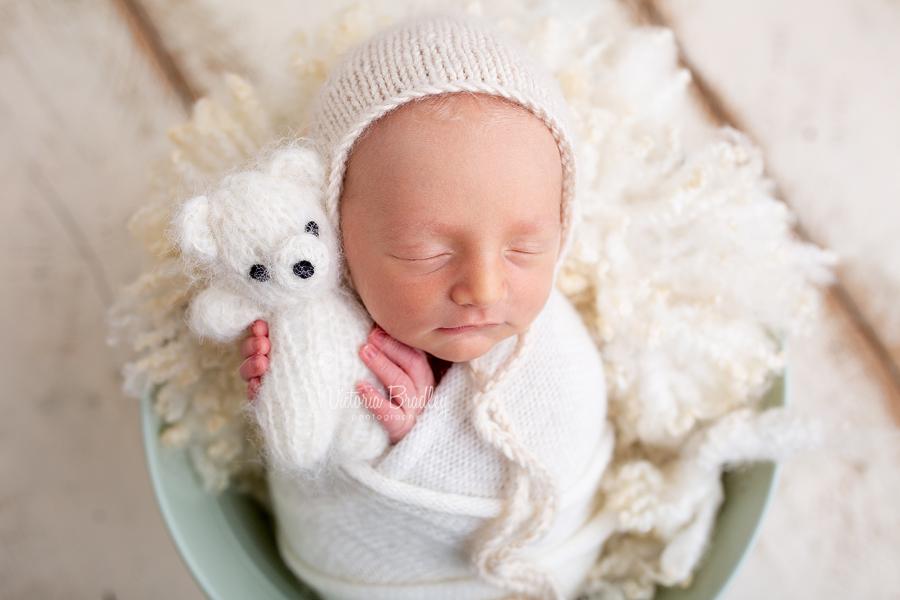 newborn holding white teddy