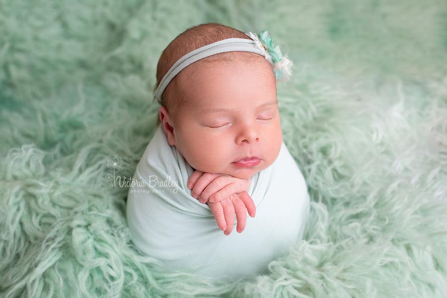 newborn baby photography girl in mint wrap on mint flokati