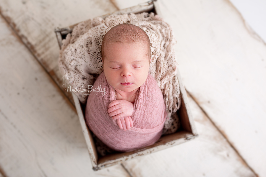 baby photography, wrapped baby in dusky pink wrap in wooden crate