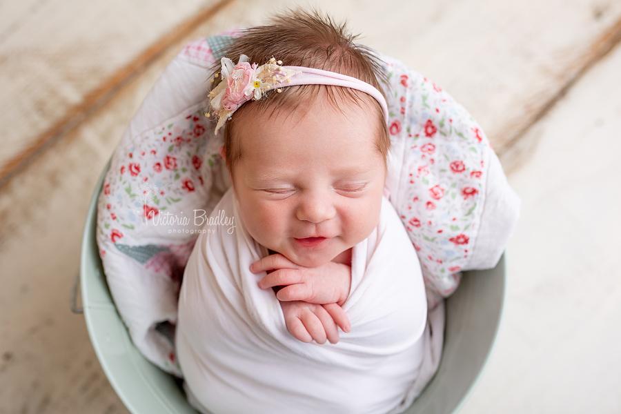 smiling baby newborn in bucket