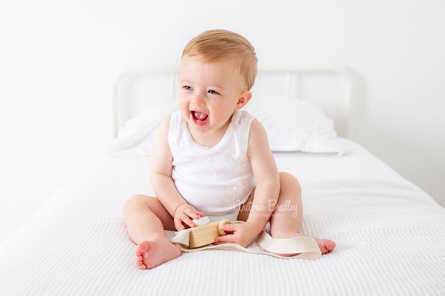 baby boy in white on white bed