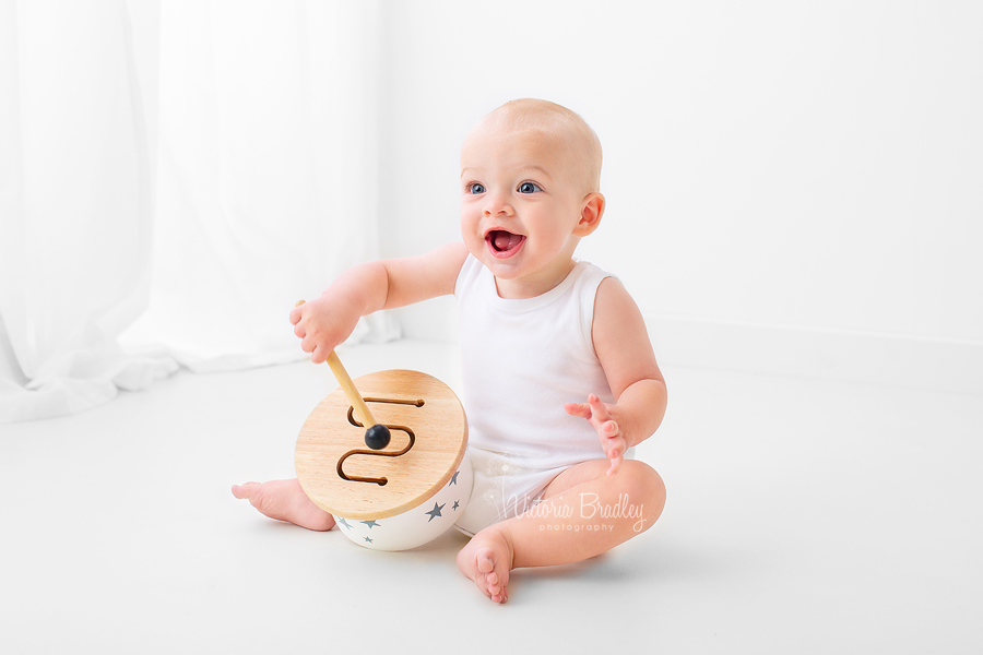 baby in white room with white drum