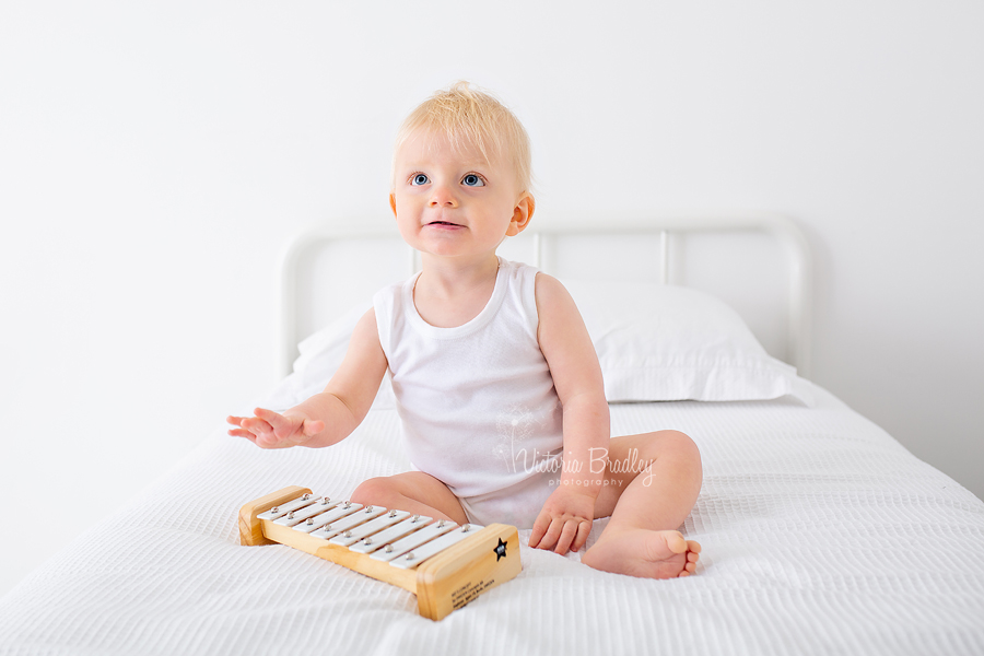 baby boy studio photography on white bed with white xylophone