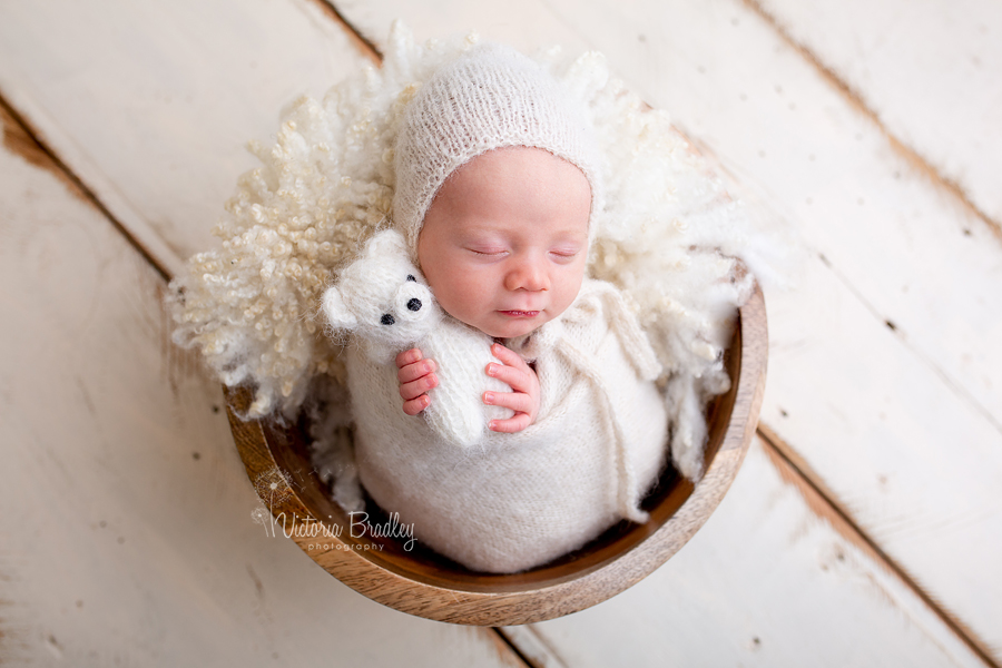 wrapped newborn baby boy with white teddy in wooden bowl