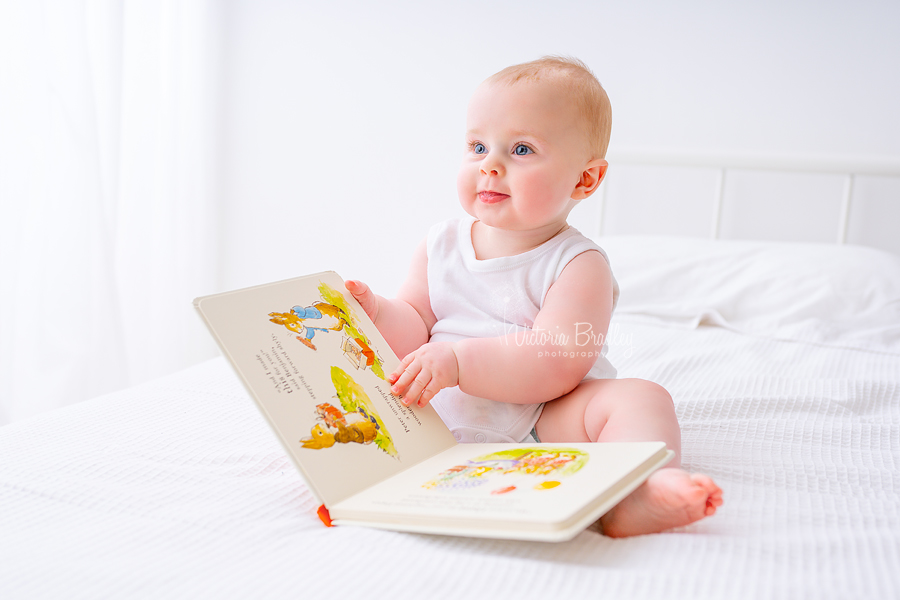 baby sitter boy reading book on white bed