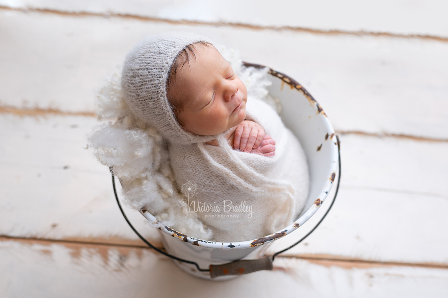 wrapped baby newborn session photography in metal bucket on cream wood floor