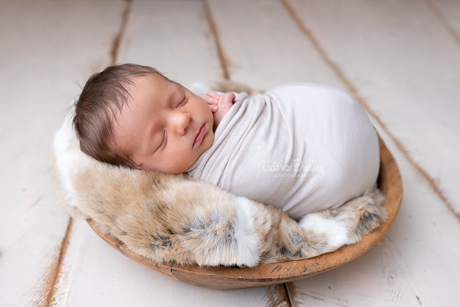 wrapped baby newborn session photography in wooden bowl on cream wood floor