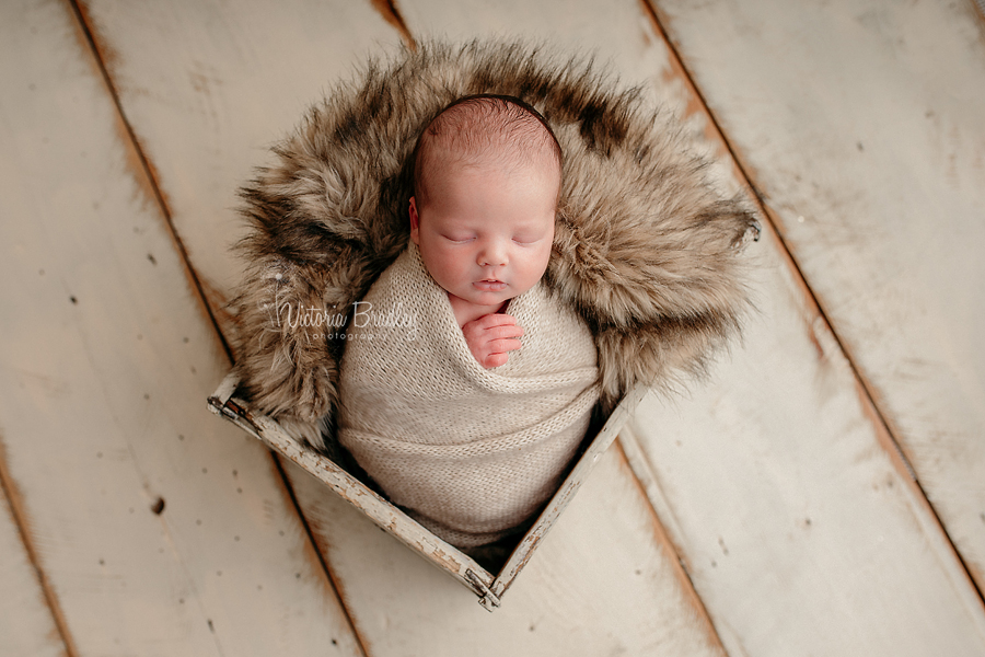 wrapped newborn baby photography, baby in crate, with fur, oatmeal wrap on cream wooden floor